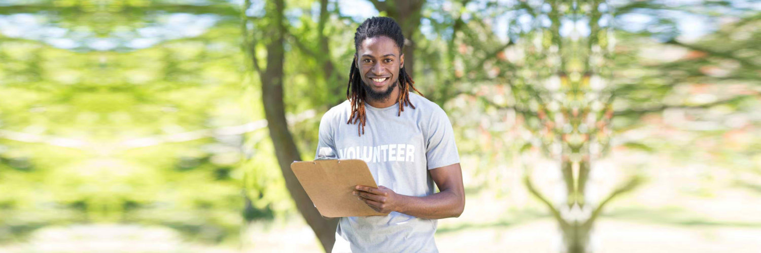 volunteer holding clip board while smiling